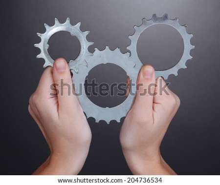 Man holding some of old metallic cogwheels in his hands - stock photo