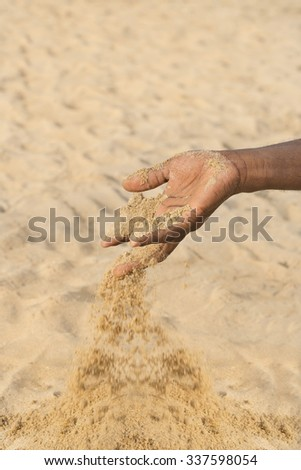 Man holding some sand in the hand: drought and desertification  - stock photo