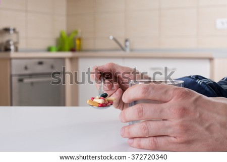 Man holding spoon with many different pills and glass of water at white kitchen table - stock photo