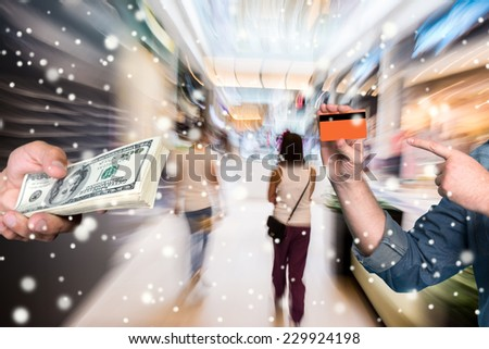 Man holding stack of dollar bills, another man holding credit card at shopping mall.  Christmas and holidays concept  - stock photo