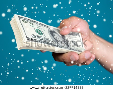 Man holding stack  of dollar bills on a blue background.  Christmas and holidays concept  - stock photo
