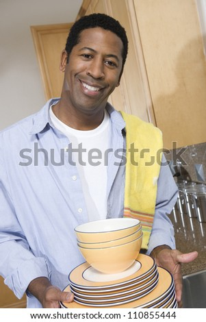 Man Holding Stack Of Washed Plates - stock photo