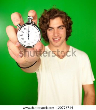 Man Holding Stopwatch On Green Background - stock photo