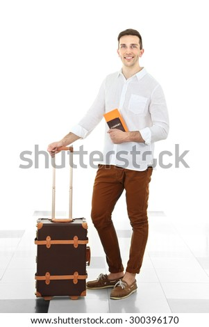 Man holding suitcase in airport - stock photo