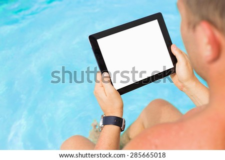 Man holding tablet computer by the swimming pool - stock photo