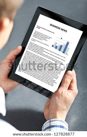 man holding tablet computer with business text on the screen