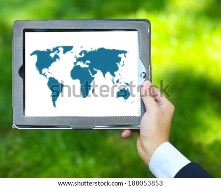 Man holding tablet computer with world map on the green grass background