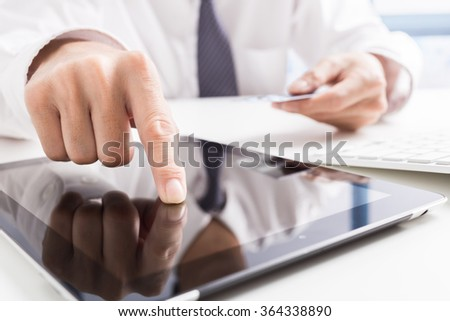 Man holding tablet pc and credit card indoor. Shopping Online