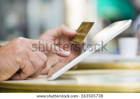 Man holding tablet pc and credit card on coffee terrace, Shopping on-line - stock photo