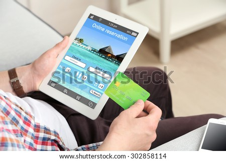 Man holding tablet with screen interface of booking hotels - stock photo