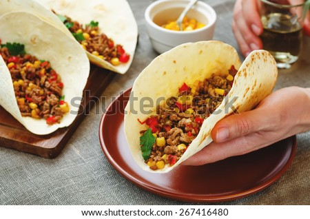Man holding tacos with meat, corn and peppers. tinting. selective focus - stock photo