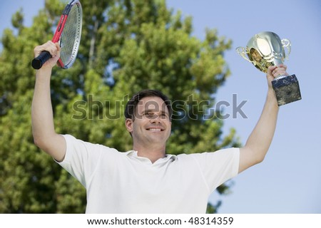 Man Holding Tennis Rackets and Trophy