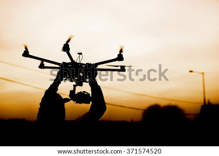 Man holding the drone, preparing for take off. Silhouette against the sunset sky.
