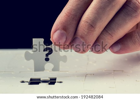 Man holding the final puzzle piece with a question mark hand-drawn on it in his fingers above a jigsaw puzzle conceptual of a problem and the solution. - stock photo