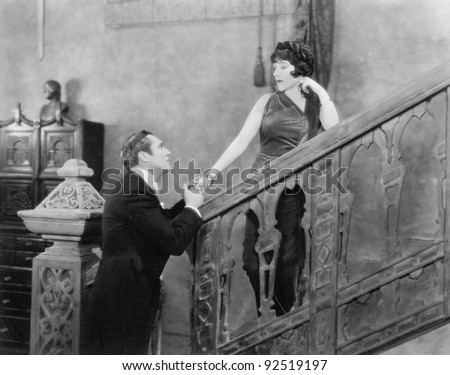 Man holding the hand of a woman standing on a staircase
