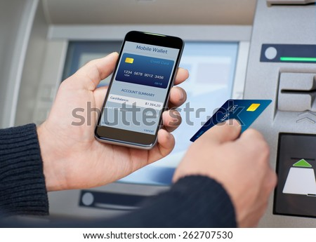 man holding the phone with mobile wallet and credit card on the screen against the background of the ATM