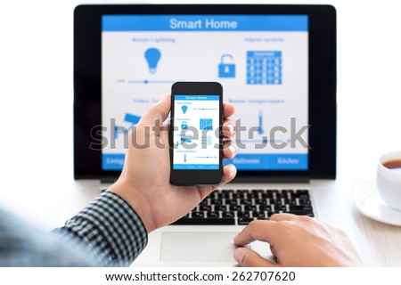 man holding the phone with program smart home on the screen against the background of the computer - stock photo
