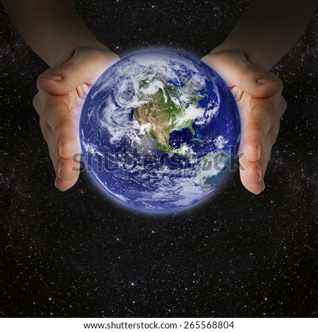man holding the planet earth in the hands against the background of the galaxy. Elements of this image furnished by NASA - stock photo