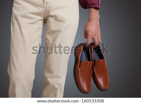 Man holding the shoes in hand close up  - stock photo