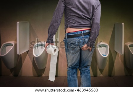 Man holding toilet paper roll and holding his butt in restroom. Diarrhea concept.