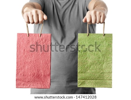 man holding two shopping bags isolated on white background. choice concept