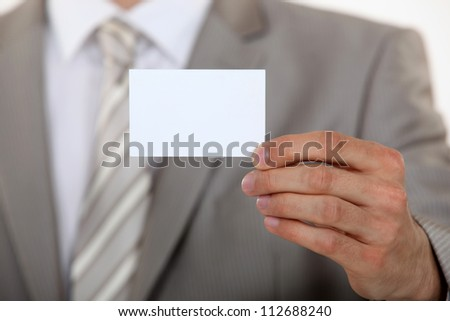 Man holding up a blank business card - stock photo
