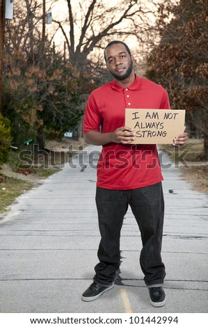 Man holding up a sign that says I am not always strong
