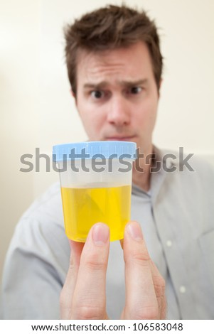 MAN HOLDING URINE SAMPLE FOR DRUG TEST - stock photo