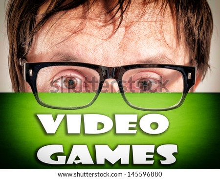 Man holding video games over his face - stock photo