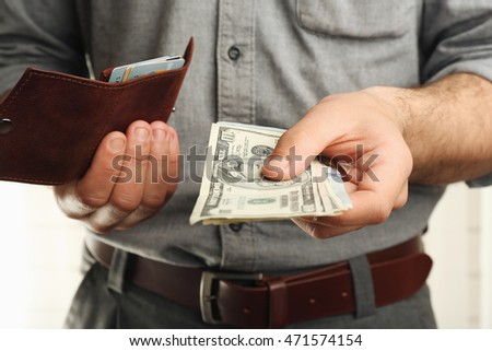 Man holding wallet with money, closeup