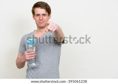 Man holding water bottle and pointing finger at you