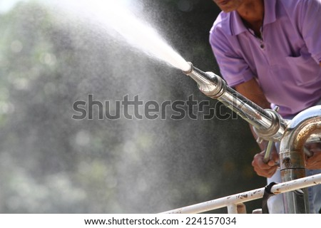 Man holding water hose to prevent fire on car - stock photo