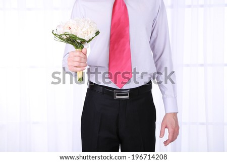 Man holding wedding bouquet on light background