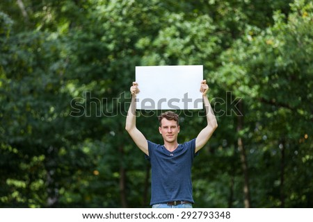 Man holding white board in the park - stock photo