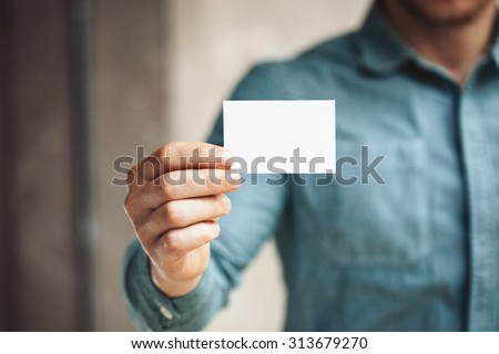 Man holding white business card on concrete wall background - stock photo