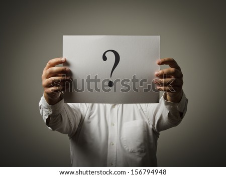 Man holding white paper with question-mark. Man having no answers to a question. - stock photo