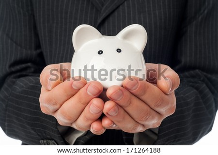 Man holding white piggy bank over black suit background. - stock photo