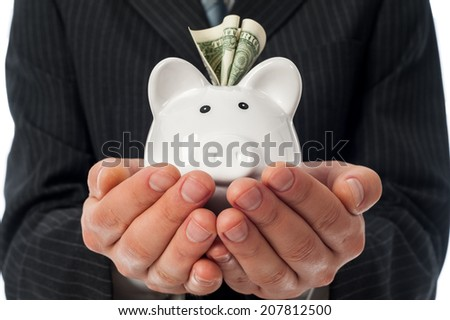Man holding white piggy bank with dollar inside over black suit background. - stock photo
