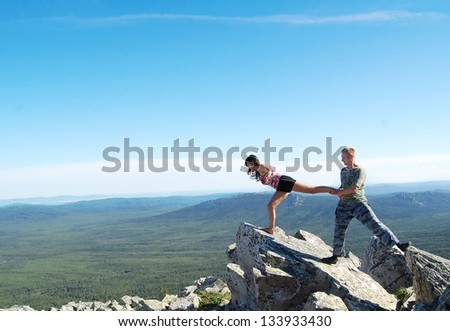 Man holding woman by leg and standing on mountain - freedom concept - stock photo