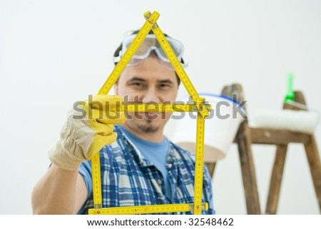 Man holding yellow folding ruler shaped in form of house. Isolated on white background. Selective focus on ruler. - stock photo