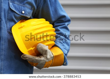 Man holding yellow helmet close up, shallow dof