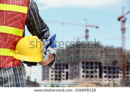 man holding yellow helmet in front of construction site - stock photo