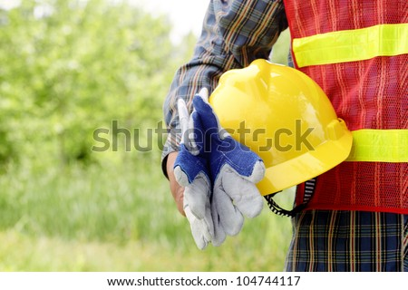 man holding yellow helmet in the outdoors