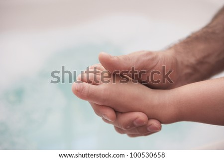 Man holding young child's foot
