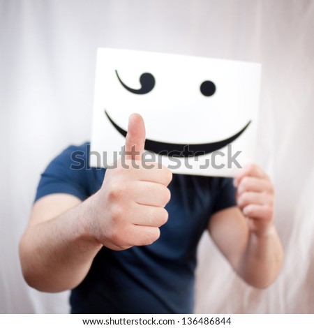 man holds a smile, thumbs up - stock photo