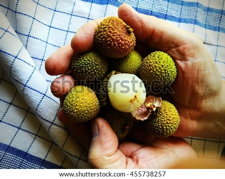 Man holds fresh lychees, one peeled