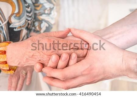 Man holds hands of eldery woman. Senior help concept. - stock photo