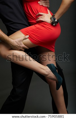 Man holds leg of female in red dress and high-heeled shoes - stock photo