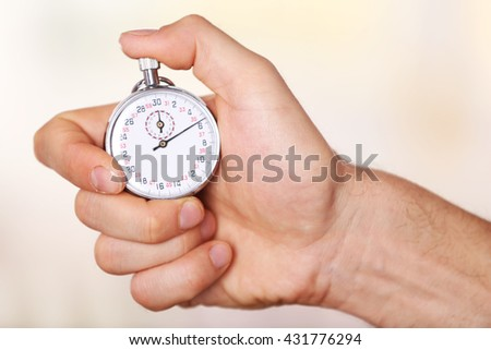Man holds stopwatch in hand, close up - stock photo