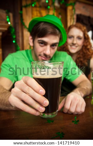Man holds up a pint of stout in a St. Patrick's Day themed pub. - stock photo